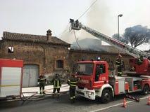 Brandmän är upptagna att släcka en brand i ett gammalt hus Arkivfoto