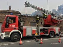 Brandmän är upptagna att släcka en brand i ett gammalt hus Arkivbilder