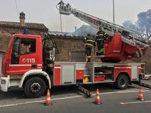 Brandmän är upptagna att släcka en brand i ett gammalt hus Arkivbild