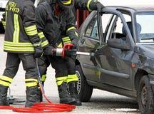 Brandmän öppnar dörren med kraftig pneumatisk sax Arkivbilder