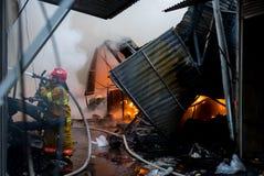 Brandmän arbetar på en brand av byggnad genom att använda ett hjälpmedel för metallskärareräddningsaktion under en brand Brand sl Royaltyfri Bild