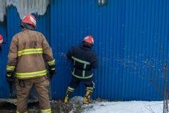 Brandmän arbetar på en brand av byggnad genom att använda ett hjälpmedel för metallskärareräddningsaktion under en brand Brand sl Royaltyfri Foto