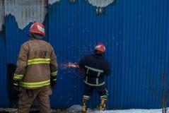 Brandmän arbetar på en brand av byggnad genom att använda ett hjälpmedel för metallskärareräddningsaktion under en brand Brand sl Arkivbilder