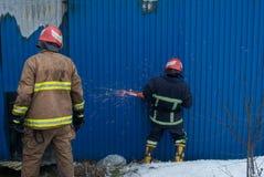 Brandmän arbetar på en brand av byggnad genom att använda ett hjälpmedel för metallskärareräddningsaktion under en brand Brand sl Arkivfoto