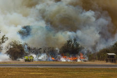 Brandmän besprutar flammar som internationell flygplats för den skogsbrandslutSan Salvador Royaltyfria Bilder