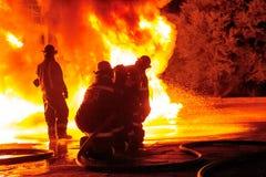 Brandmän i belägen mitt emot vit varm inferno för bunkerkugghjul Arkivfoto