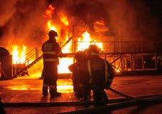 Brandmän i belägen mitt emot vit varm inferno för bunkerkugghjul med att bölja rök Arkivbild