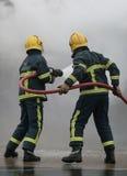 Brandmän med slangen Arkivfoton