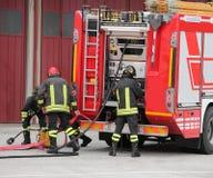 Brandmän och brandlastbilen under en periclesbeskickning Royaltyfri Foto