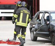Brandmän och förstörd bil efter olyckan Arkivfoto