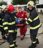 Brandmän och räddare som tar bort sårat på en bår förbi Royaltyfria Foton