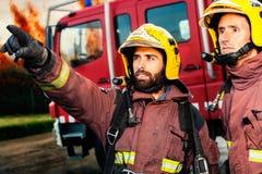 Brandmän omkring som tar handling Arkivfoto
