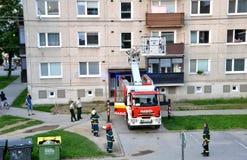 Brandmän på början av handling står med två poliser bredvid brandlastbilen Royaltyfri Bild