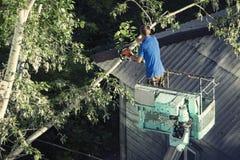 Brandmän på den utsträckbara kranen som klipper filialer av ett träd för säkerhetsanledningar efter tungt snöfall royaltyfri fotografi