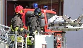 brandmän på korgen för brandlastbilen sparar de sårade personwina Royaltyfria Foton