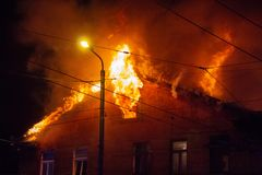 Brandmän riktar vattenströmmen på bränninghus oavkortad flammande inferno för byggnad och en brandmanstridighet som får kontroll  royaltyfri foto