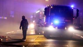 Brandmän riktar vattenströmmen på bränninghus oavkortad flammande inferno för byggnad och en brandmanstridighet som får kontroll  arkivfilmer