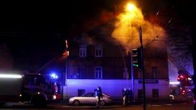 Brandmän riktar vattenströmmen på bränninghus oavkortad flammande inferno för byggnad och en brandmanstridighet som får kontroll  stock video