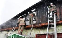 Brandmän släcker en brand på taket Royaltyfria Bilder