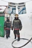 Brandmän släcker en brand på taket Royaltyfria Foton