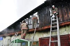 Brandmän släcker en brand på taket Arkivbilder