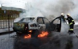 Brandmän släcker en brinnande bil i Ryssland Arkivbild