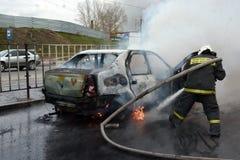 Brandmän släcker en brinnande bil i Ryssland Royaltyfria Foton
