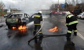 Brandmän släcker en brinnande bil i Ryssland Royaltyfria Bilder