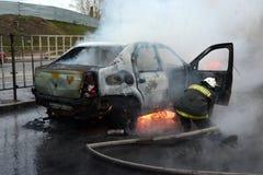 Brandmän släcker en brinnande bil i Ryssland Royaltyfri Foto
