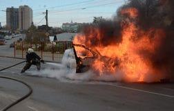 Brandmän släcker en brinnande bil i Ryssland Arkivfoto