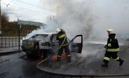 Brandmän släcker en brinnande bil i Ryssland Arkivfoton