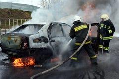 Brandmän släcker en brinnande bil i Ryssland Fotografering för Bildbyråer