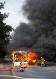 Brandmän släcker en brinnande buss Royaltyfri Fotografi