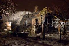 Brandmän släcker huset Natten snöar det royaltyfri foto