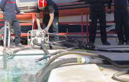 Brandmän som arbetar med en sugpump royaltyfri foto