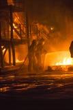 Brandmän som arbetar på brand Arkivbild