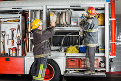Brandmän som arbetar på lastbilen i brandstation Royaltyfri Foto