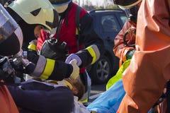 Brandmän som behandlar en sårad person royaltyfria bilder