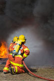 2 brandmän som besprutar vatten i brandstridighet med brand- och mörkersmo Arkivbild