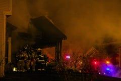 Brandmän som bryter in i ett brinnande hus Royaltyfri Bild