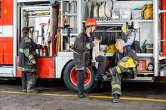 Brandmän som diskuterar med lastbilen Arkivbilder