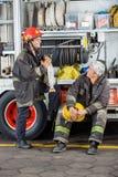 Brandmän som diskuterar med lastbilen på brandstationen Arkivfoto