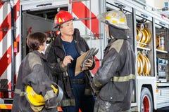 Brandmän som diskuterar mot lastbilen på brand Arkivbilder