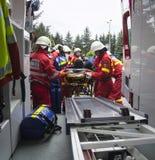 Brandmän som får offret i ambulans Arkivbild