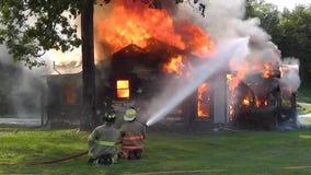 Brandmän som försöker att kontrollera flammorna av ett hus, avfyrar. arkivfilmer