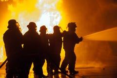 Brandmän som kontrollerar slangen som besprutar vatten under brandbekämpningövning Arkivbilder