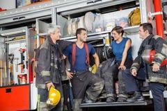 Brandmän som meddelar vid firetrucken på stationen Fotografering för Bildbyråer