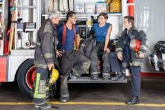 Brandmän som samtalar på brandstationen arkivbild