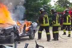 Brandmän som släcker bilen på brand arkivfoto