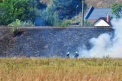 Brandmän som slåss lös brand arkivbilder